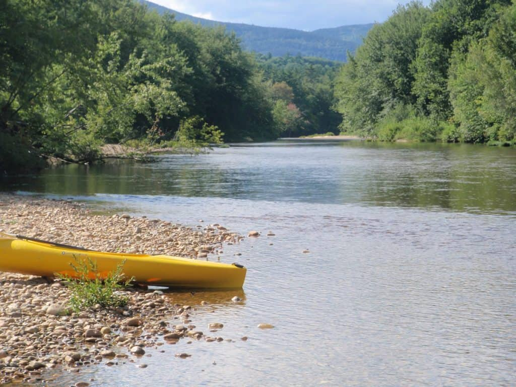 an empty kayak sitting alongside the shore of a river