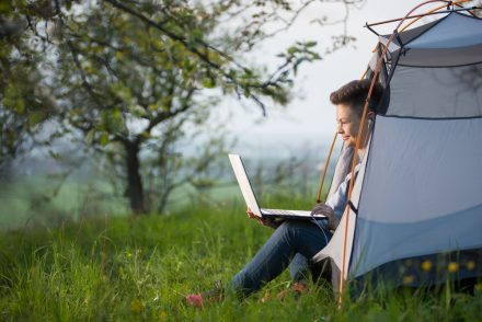 a woman sitting inside a tent with her feet outside and her laptop open and using it
