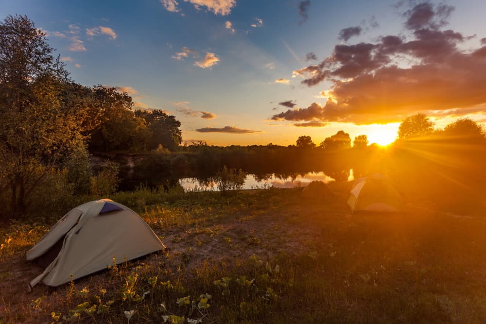 a bright sunset with two tents in the foreground